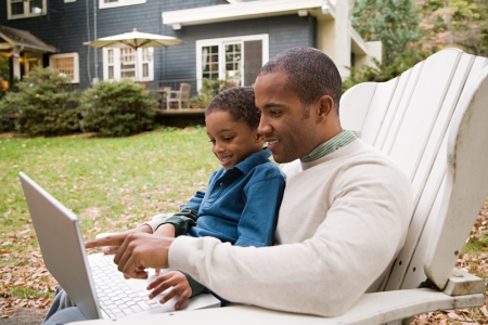 Father and son with computer outside